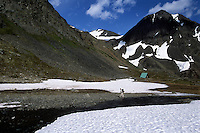 A hiker on the Crow Pass Trail passes snow melting into a creek flowing out of Crow Pass, high in the Chugach Mountains near Girdwood, Alaska. At right is a public use cabin that can be rented for overnight stays in the Chugach National Forest.