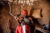 Ropinho Cassuada (40) holds a pair of antelope horns during a spiritual ceremony. Ropinho used to work in the Bank of Mozambique in Tete town until he was possessed by a spirit, who forced him to leave the job, move to the countryside and become a witchdoctor.