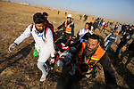 """A wounded Palestinian protester is evacuated during clashes with Israeli troops following the tents protest where Palestinians demand the right to return to their homeland at the Israel-Gaza border, in the southern Gaza Strip, April 19, 2019. The Palestinian health ministry in Gaza later said in a statement that 46 people were wounded by Israeli fire during border demonstrations, including """"five paramedics and four journalists"""". Photo by Ashraf Amra"""