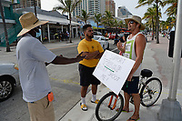 """FORT LAUDERDALE, FL - JUNE 28: A Man is seen holding a sign that reads """"I support trump don't shoot me"""" is engaging with others on Fort Lauderdale Beach as South Florida beaches are to close for July Fourth weekend, Florida reports another record spike in coronavirus cases, Floridaís Covid-19 surge shows the state's reopening plan is not working on June 28, 2020 in Fort Lauderdale Beach, Florida. Credit: mpi04/MediaPunch"""