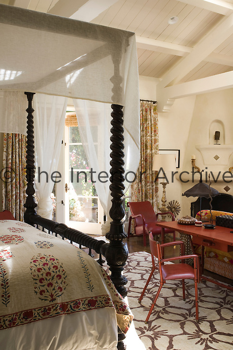In the master bedroom the red pattern in the Indian bedcover harmonises with the red metal table and chairs