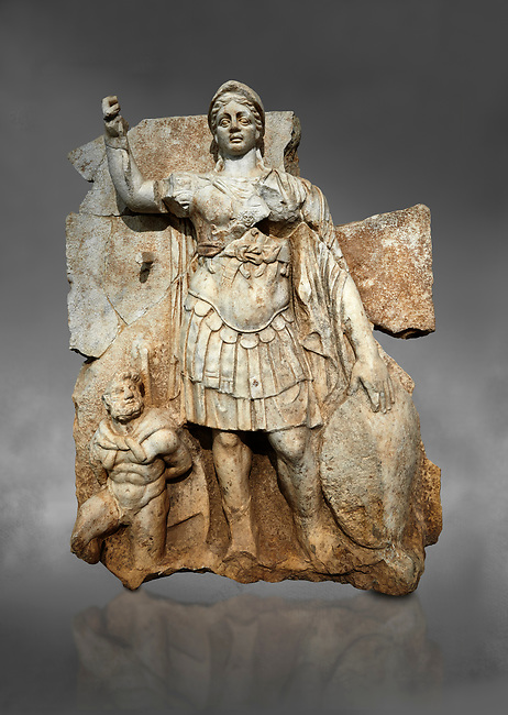 Roman Sebasteion relief  sculpture of Roma armed, Aphrodisias Museum, Aphrodisias, Turkey.  Against a grey background.<br /> <br /> Roma is equipped with a spear, helmet, round shield and imperial style armour. Blow crouches a naked bearded prisoner, with hands tied behind his back and a skin knotted around his neck. He turns to look up at Roma