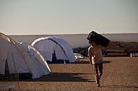 Tunisie pres du Djiba Camp UNHCR de refugies libyens a la frontiere entre Tunisie et Libye , libyens en attent d'etre envoyes dans leur camp....Tunisia close to Djiba UNHCR refugees camp  Tunisian and Libyan border  libyan refugees waiting for their final camp destination....Tunisia nei pressi del campo profughi di Djiba al confine tra tunisia e Libia  Profughi libici appena giunti e  in attesa di essere inviati in uno dei campi profughi, un profugo con una valigia