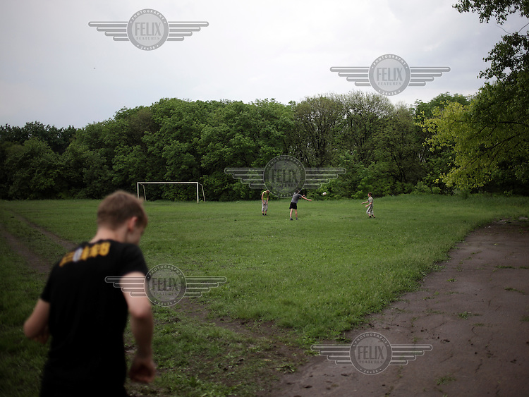 Young boys throw a rugby ball about in a park.