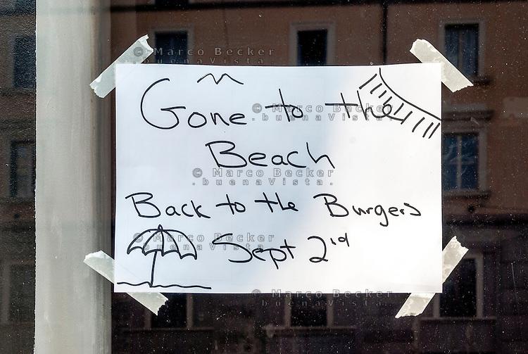 """Milano, cartello di chiuso per ferie (""""andati alla spiaggia, di ritorno agli hamburger il 2 settembre"""") sulla vetrina di un esercizio di ristorazione --- Milan, closed for vacation sign (""""gone to the beach back to the burgers sept 2nd"""") on the window of a eatery"""
