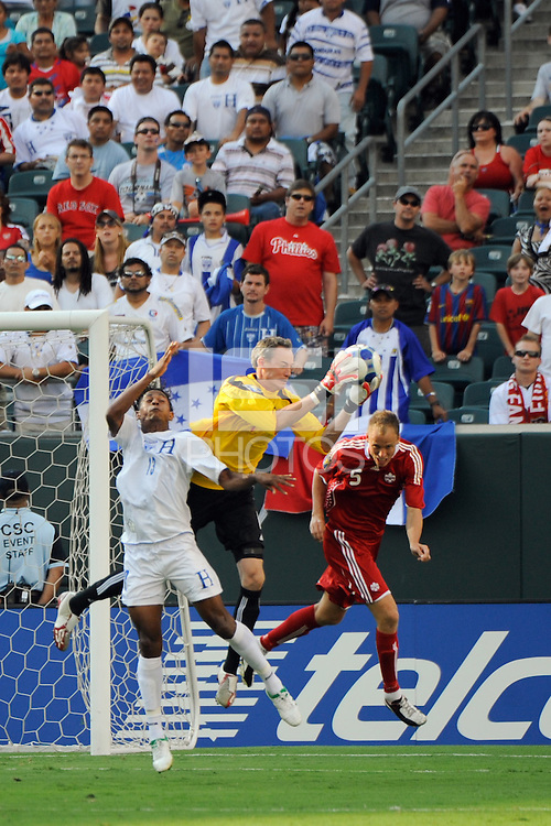 Canada (CAN) goalkeeper Greg Sutton (1) grabs a ball as Carlo Costly (13) of Honduras (HON) goes for a header. during a quarterfinal match of the CONCACAF Gold Cup at Lincoln Financial Field in Philadelphia, PA, on July 18, 2009.