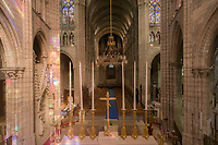 Gothic nave looking seen from the choir, with arcade, clerestory and triforium of stained glass, in the Basilique Saint-Denis, Paris, France. On the left is the funerary monument of Dagobert, 603-39, Merovingian king of France 629-39, with reliefs depicting the legend of John the Hermit, stone, c. 1264. In the centre is the new altar, by Vladimir Zbynovsky, a French-Slovakian artist, consecrated 14th January 2018. The basilica is a large medieval 12th century Gothic abbey church and burial site of French kings from 10th - 18th centuries. Picture by Manuel Cohen