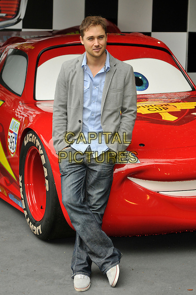 Marcus Patrick.UK Premiere of 'Cars 2' at Whitehall Gardens,  London, England..July 17th 2011.full length blue shirt grey gray suit jacket jeans denim hands in pockets.CAP/CAS.©Bob Cass/Capital Pictures.
