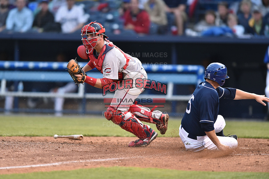 Greenville Drive catcher Jordan Procyshen (17) fields the throw and tags the plate as Kevin Padlo (15) slides home during game one of a double header against the Asheville Tourists on April 18, 2015 in Asheville, North Carolina. The Tourists defeated the Drive 2-1. (Tony Farlow/Four Seam Images)