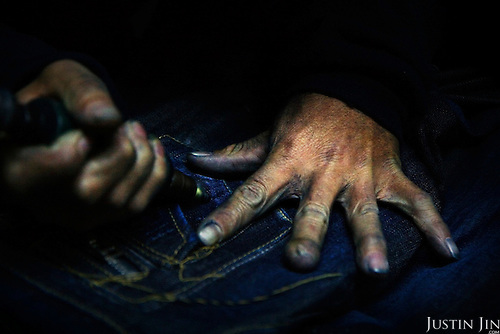 """A worker drills holes in jeans in Mr Huang's factory in Zhongshan city, China..This picture is part of a photo and text story on blue jeans production in China by Justin Jin. .China, the """"factory of the world"""", is now also the major producer for blue jeans. To meet production demand, thousands of workers sweat through the night scrubbing, spraying and tearing trousers to create their rugged look. .At dawn, workers bundle the garment off to another factory for packaging and shipping around the world..The workers are among the 200 million migrant labourers criss-crossing China.looking for a better life, at the same time building their country into a.mighty industrial power."""