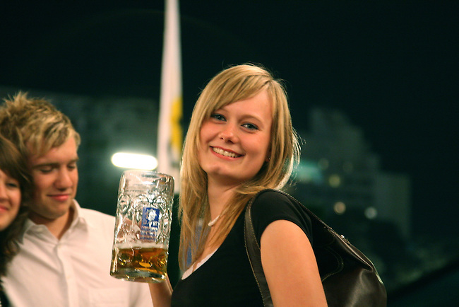 A young woman with a large beer poses for a quick snapshot during Oktoberfest in Munich, Germany. Oct. 2, 2007.