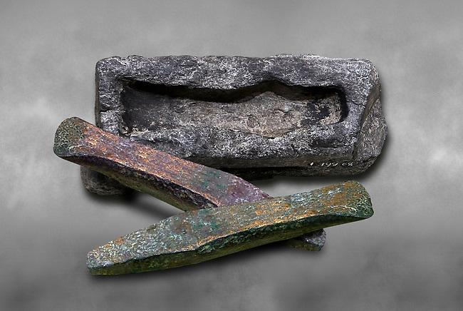 Hittite axe head mould and bronze axe heads. Hittite Period 1600 - 1200 BC. Alaca Hoyuk. Çorum Archaeological Museum, Corum, Turkey. Against a grey bacground.