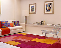 A white living room is given a note of warmth with this brightly coloured woollen rug