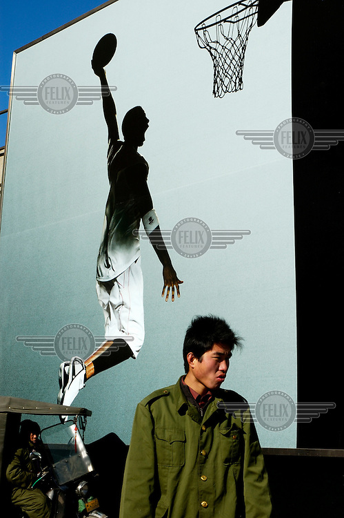 A man walks past an advertisement for Adidas featuring a basketball player. The company is an official sponsor of the 2008 Beijing Olympic Games.