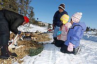 Koyuk kids watch Aliy Zirkle boot her dogs in preparation for leaving Koyuk on Monday during Iditarod 2011.