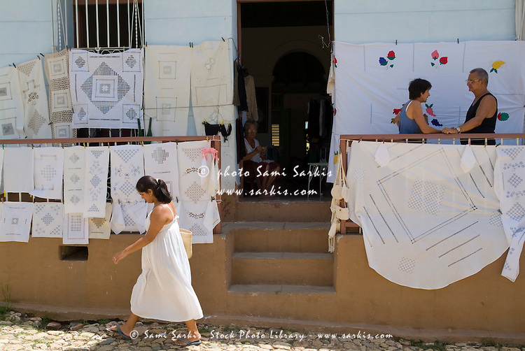 Woman looking at lace sheets and tablecloths for sale at a street market, Trinidad, Cuba.