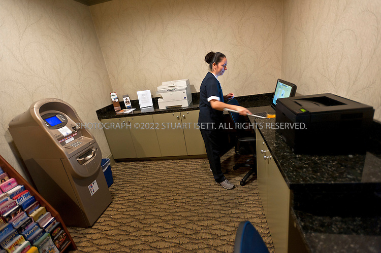 "9/27/2011--Seattle, WA, USA..Hotel employee Mayra Anguiano, 27, dusts the business center, just off the main lobby, at the Silver Cloud Hotel in Seattle, WASH. ..Business travelers armed with laptops, smartphones and wifi cards, are eschewing hotel business centers in favor of working in their rooms or the lobby, and hotels across the price spectrum have added the trappings of those business centers to where the guests are.  Hotel business centers are still used by travelers who have a document or boarding pass to print, or need to check email and don't have their laptop, but they will usually get in and out quickly, rather than spend hours working there. And the business centers themselves are likely to be small rooms with just a few computers and printers. The Silver Cloud Hotel in Seattle, part of a ten-hotel chain in the Northwest, offers up two workstations and two printers, ""and business people barely use them,"" said the hotel's general manager Chauncey DeVitis. The free WiFi and the copy machine behind the front desk seems to meet the needs of most business travelers these days, he said...©2011 Stuart Isett. All rights reserved."