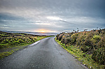 Road over moorland in english landscape with setting sun