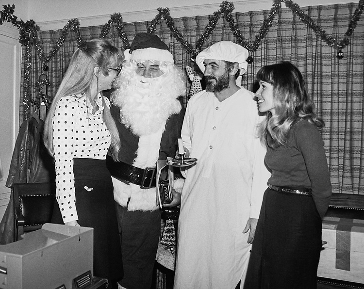 Staff members and guest having fun with Santa Claus during Christmas party. (Photo by CQ Roll Call via Getty Images)