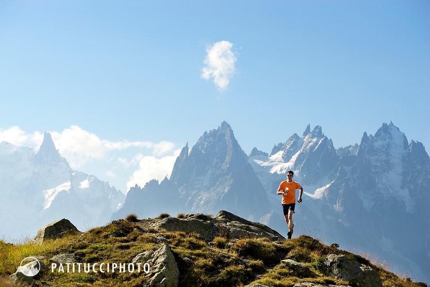 Trail runner on the scenic trails above the Chamonix valley with the Aiguilles behind