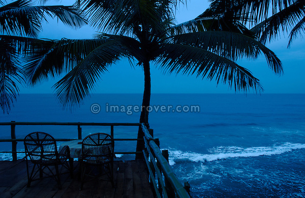 India, Kerala, Varkala Beach. Nighttime on romantic terrace with two chairs and palm trees at Varkala Beach.