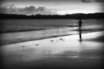 A woman in a blur running into the ocean, a grainy surreal scene.