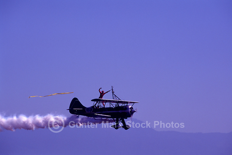 Wingwalker wingwalking on Biplane - at Abbotsford International Airshow, BC, British Columbia, Canada