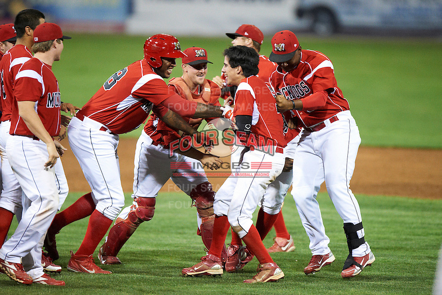 Batavia Muckdogs Steve Ramos #5 is mobbed by teammates including David Washington, Adam Lewis, and Roberto De La Cruz after a game winning walk off hit during a NY-Penn League game against the Mahoning Valley Scrappers at Dwyer Stadium on August 22, 2012 in Batavia, New York.  Batavia defeated Mahoning Valley 3-2.  (Mike Janes/Four Seam Images)