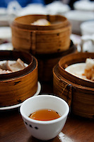 A cup of tea sits in front of steamer baskets at Dim Sum, or Yum Cha, at Lin Heung Tea House, Hong Kong