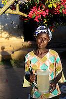 KENIA, ADS Anglican Development Services of Mount Kenya East, Stadt Embu, Dorf Gichunguri, Projekt Regenwasserauffang an einem Felsen und Speicherung in Tanks zur Nutzung in Duerreperioden, Agnes Irima, 44 Jahre, auf ihrem Hof mit Wasserkanne