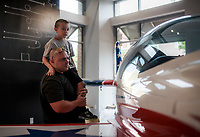 NWA Democrat-Gazette/CHARLIE KAIJO Jason Stouder of Bentonville holds up Allan Stouder, 7 to get a better look at an XA42 airplane, Friday, July 6, 2018 at the OZ1 Flying Club pop-up shop in Bentonville. <br /><br />A pop-up center hosted by several aviation groups opened in downtown Bentonville with the goal of increasing accessibility to aviation throughout Northwest Arkansas.There is an XA42 plane in the building as well as several displays with videos, photos and information. Organizers hope it will generate excitement about the new flight center, which is schedule to open in September and be accessible to the general public, not just the aviation community.