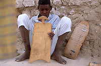 Young Islamic students recite and write on wood tablets passages from the Koran during a class held on a street in Timbuktu, Mali, Jan. 8, 2008.