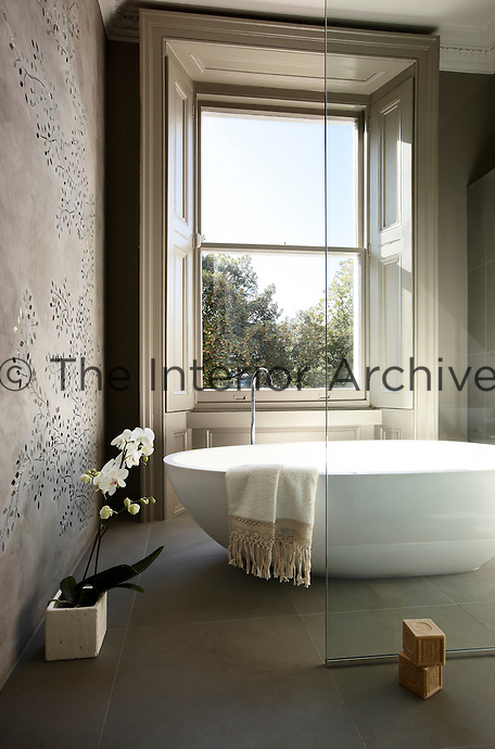 An elegant freestanding bath in a contemporary bathroom, which contrasts with the orginal Victorian-era window complete with shutters. The wall is decorated with glass mosaic tiles in a floral pattern.