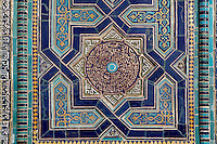 "Detail of octagonal star decoration, ""Nameless 1"" Mausoleum, 1380s, Shah-I Zinda ensemble, Samarkand, Uzbekistan, pictured on July 19, 2010, in the morning. The Shah-i-Zinda Complex is a necropolis of mausoleums whose legendary origin dates back to 676 when Kussam-ibn-Abbas arrived to convert the locals to Islam. So successful was he that he was assassinated whilst at prayer. His grave remains the centre of the sacred site which grew over many centuries, especially the 14th and 15th, into an architecturally stunning  example of ceramic art. This Mausoleum, created by Usto Alim Nesefi, is decorated  with relief painted majolica. The portal decorations are notable for the symbol of ""octagonal stars"". Samarkand, a city on the Silk Road, founded as Afrosiab in the 7th century BC, is a meeting point for the world's cultures. Its most important development was in the Timurid period, 14th to 15th centuries. Picture by Manuel Cohen."