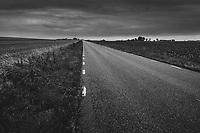 Dyster landsväg i platt landskap i mulet väder i Österlen Skåne i svartvitt