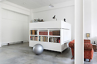 The extra bed folds away into the wall of the open plan living area, next to the study on wheels