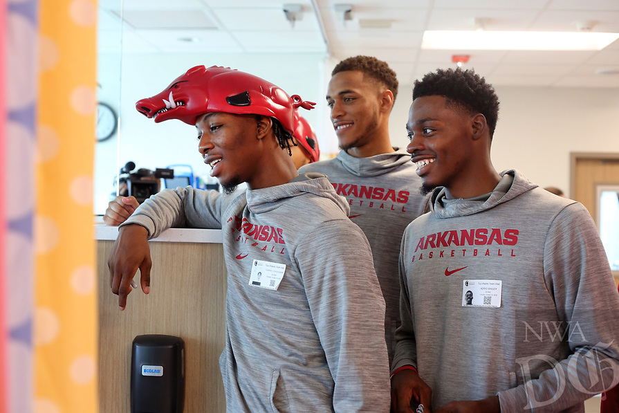 NWA Democrat-Gazette/DAVID GOTTSCHALK Gabriel Osabuohien (left), a member of the University of Arkansas Razorbacks' mens basketball team, smiles Tuesday, October 16, 2018, with teammates as they visit patients at Arkansas Children's Northwest in Springdale. The team and staff visited patients at the hospital, greeted people as they entered and cleaned a variety items during their visit.