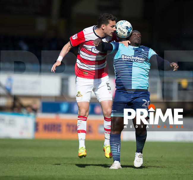 Mathieu Baudry of Doncaster Rovers battles with Adebayo Akinfenwa of Wycombe Wanderers during the Sky Bet League 2 match between Wycombe Wanderers and Doncaster Rovers at Adams Park, High Wycombe, England on 22 April 2017. Photo by James Williamson / PRiME Media Images.