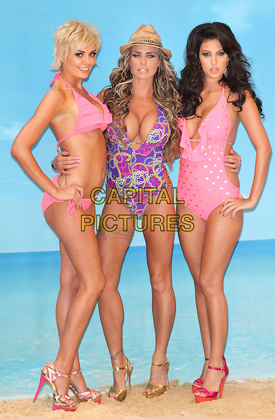 Orlaith McAllister, Katie Price and Ellie Jenas.Katie Price (Jordan) launches her new swimwear range - Katie's Boutique for Store 21 - at The Worx Studios, London - March 7th 2012.full length straw hat bathing suit swimsuit purple pink yellow print hand on hip gold plunging neckline cleavage pink bikini stars print side gold sandals .CAP/ROS.©Steve Ross/Capital Pictures