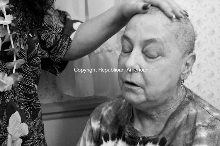 MIDDLEBURY, CT - 24 DECEMBER 2007 -112008JT22-<br /> Tracie Marcil places her hand on her mother Marie Tyrrell's head after shaving her mother's head at Marie's house in Middlebury on Christmas Eve 2007. Having gone through her fourth round of chemotherapy, this was Marie's second time having her head shaved since being diagnosed with stage four lung cancer. The hair cut followed a tropical-themed Christmas party at the empty house that was put up for sale after Marie was diagnosed.<br /> Josalee Thrift / Republican-American
