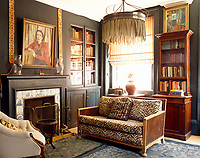 A tiger-skin print covering the antique sofa adds a sensual touch to this darkly dramatic study in a Georgian house in Spitalfields