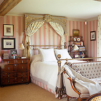 A Victorian brass bedstead has been given a sense of drama with the addition of a giltwood pelmet and curtains on the striped wallpaper of this bedroom
