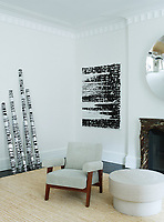 The living room is airy and graciously proportioned and is furnished with a mix of vintage and more modern pieces. The original mantel is flanked by paintings by Glenn Ligon and a pair of circa-1950s Pierre Jeanneret chairs; the central wall sculpture is by Anish Kapoor, and the table/sculpture beneath it is by Jenny Holzer.