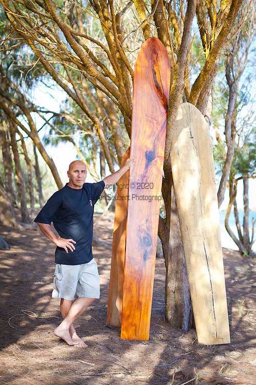 "Tom Pohaku Stone, a native Hawaiian surfer and waterman, also has a masters degree in Pacific Islands Studies.  He has revived the art of carving traditional ""wave sliding"" boards (surfboards) and Hawaiian sleds.  He is pictured here with three of his hand crafted boards made from three different kinds of native wood."