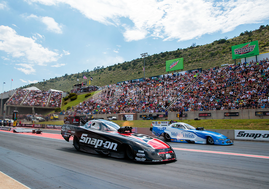 Jul 21, 2019; Morrison, CO, USA; NHRA funny car driver Cruz Pedregon (near) alongside Tommy Johnson Jr during the Mile High Nationals at Bandimere Speedway. Mandatory Credit: Mark J. Rebilas-USA TODAY Sports