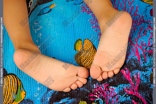 Little girl feet on a blue beach towel. 5-year old child having a rest after swimming. Healthy lifestyle and leisure activities recreation and relaxation colorful concept