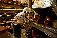 Chef tends to baby pig in open oven, Botín Restaurant, Madrid, Spain . Oldest restaurant in the world, 1725.