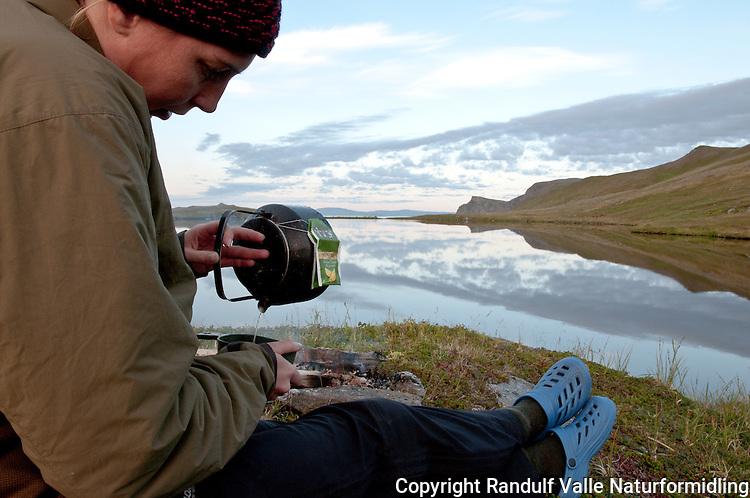 Dame skjenker te fra bålkjele. ---- Woman preparing a cup of tea.