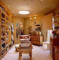 An organised walk-in dressing room is lined with floor to ceiling shelves and an assortment of chests of drawers