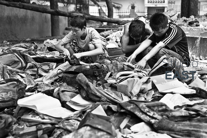 Three young boys examine the contents of schoolbags that were recovered from the rubble of Juyuan Middle School, in Juyuan county, Sichuan province, China, on May 24, 2008. The death toll from China's earthquake on May 12 rose to 69,016 as of Sunday, June 1, a report from the China's Information Office of the State Council said. In addition, 368,545 were injured and 18,830 others were still missing in the 8.0-magnitude quake that jolted southwestern Sichuan Province and some neighboring areas. Photo by Chad Ingraham/Pictobank